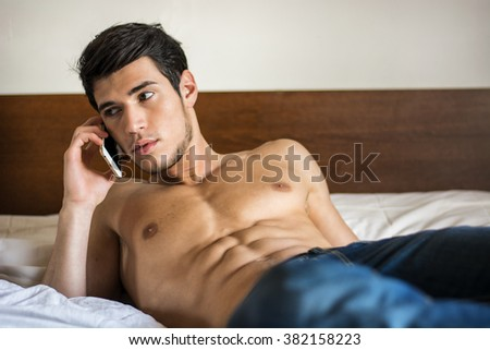 Handsome young man in bed typing on cell phone, sending text message or dialing number - stock photo