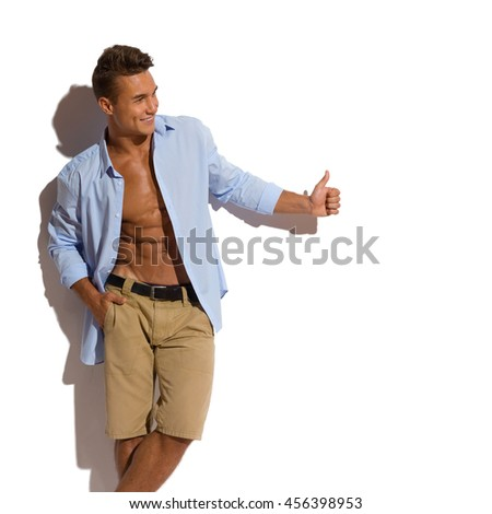 Handsome young man in beige shorts and blue unbuttoned shirt standing relaxed against sunny wall and looking away and showing thumb up. Three quarter length studio shot on white background - stock photo