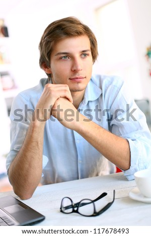 Handsome young man in blue office shirt thinking about future - stock photo
