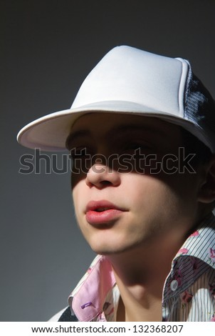 Handsome young man in cap - close up portrait - stock photo