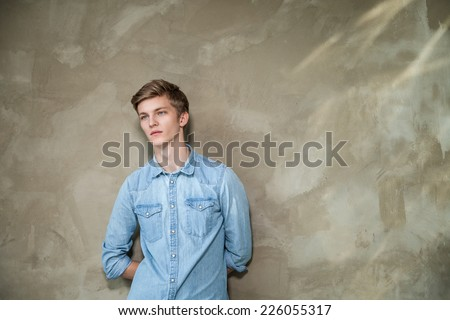 Handsome young man in casual wear standing against grey background - stock photo