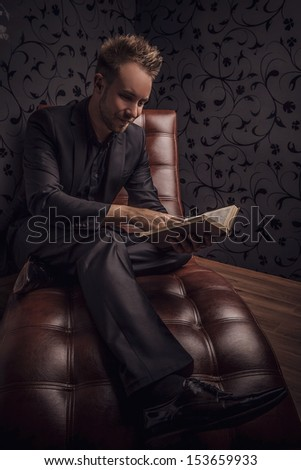 Handsome young man in dark suit relaxing on luxury sofa with book. - stock photo