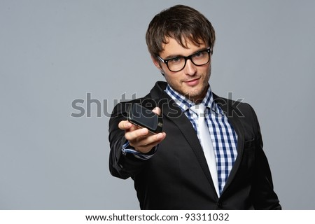 Handsome young man in glasses with mobile phone - stock photo