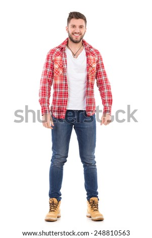 Handsome young man in jeans and lumberjack shirt standing and smiling. Full length studio shot isolated on white. - stock photo