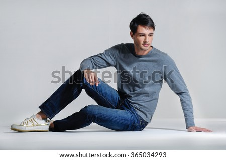 Handsome young man in jeans sitting on the floor - stock photo