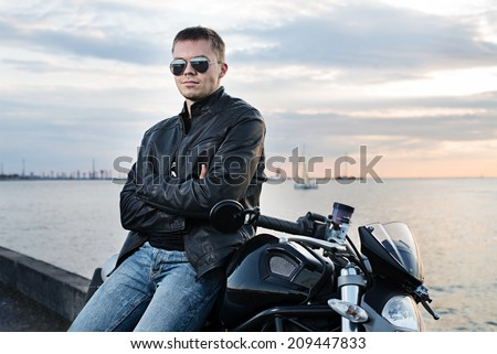 Handsome young man in leather jacket on motorcycle on sunset light on the sea embankment. - stock photo