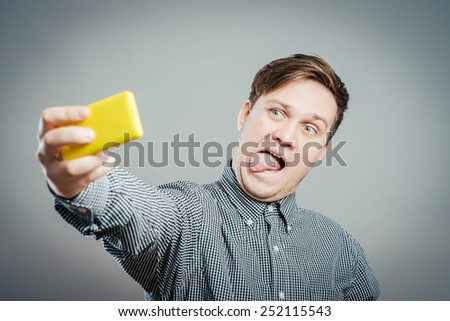 Handsome young man in shirt holding camera and making selfie and smiling while standing against grey background - stock photo