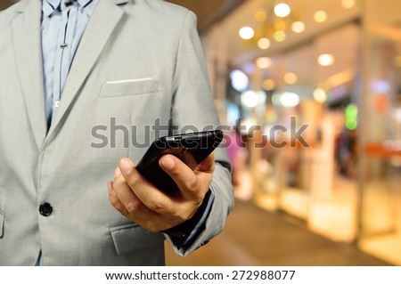 Handsome young man in shopping mall using mobile phone.  Selective focus on Phone and Hand. - stock photo