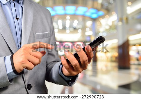 Handsome young man in shopping mall using mobile tablet.  Selective focus on Tablet in Hand. - stock photo
