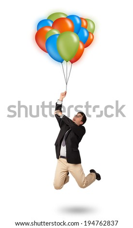 Handsome young man in suit holding colorful balloons - stock photo