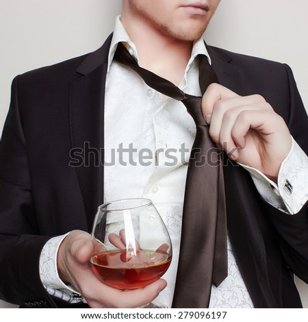 handsome young man in suit tasting with glass of alcohol isolated on white background - stock photo