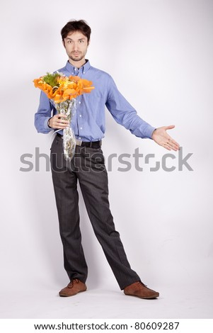 handsome young man in the blue shirt is stretched out a hand and another hand holding a beautiful bouquet of orange packing - stock photo