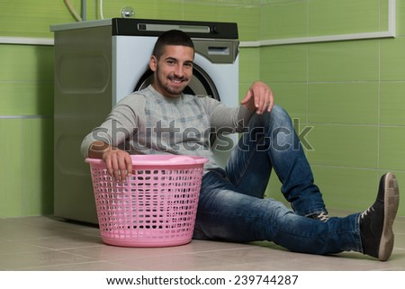 Handsome Young Man In The Laundry Room - stock photo