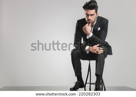 Handsome young man in tuxedo sitting on a stool while thinking, holding one hand to his chin. - stock photo