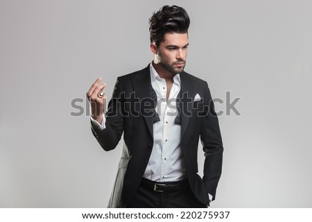 Handsome young man in tuxedo snapping his finger while looking away from the camera. On grey background. - stock photo