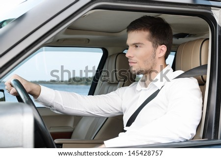 Handsome young man in white shirt driving the car holding the right hand on the wheel - stock photo