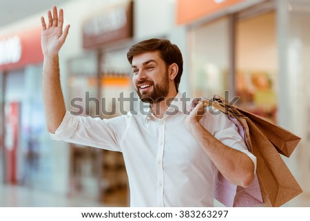 Handsome young man in white shirt holding shopping bags, waving and smiling while standing in mall - stock photo