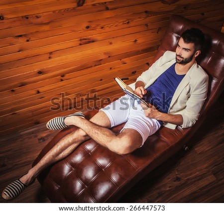Handsome young man in white suit relaxing on luxury sofa with diary.  - stock photo