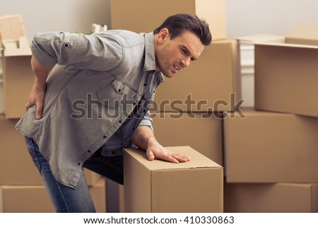 Handsome young man is moving, having pain in his back while packing, standing among cardboard boxes - stock photo