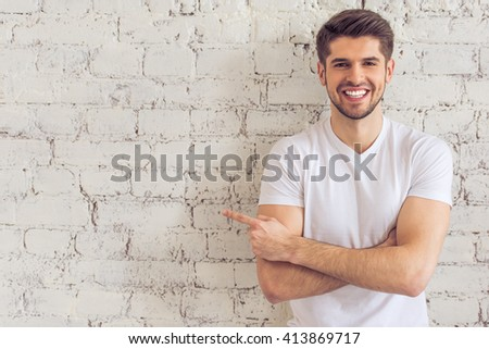 Handsome young man is pointing away, looking at camera and smiling, standing against white brick wall - stock photo