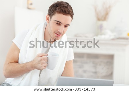 Handsome young man is using laptop in his bedroom. He is drinking coffee and smiling. The man is sitting with a white towel on his neck - stock photo