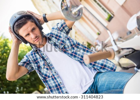 Handsome young man is wearing helmet while sitting on scooter. - stock photo