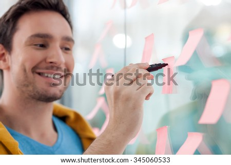 Handsome young man is working with joy. He is standing and writing on sticker with inspiration. The designer is smiling - stock photo