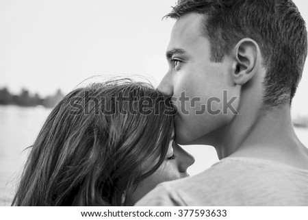 Handsome young man kissing his girlfriend near the river black and white - stock photo