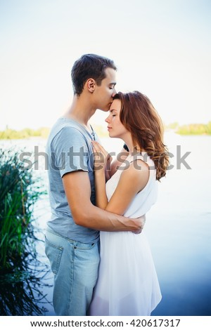 Handsome young man kissing his girlfriend on the forehead near the river. The man buried his nose in the girl's hair. Ð¡lose your eyes and dream - stock photo