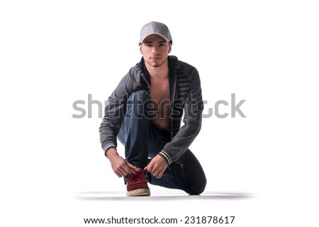 Handsome young man kneeling and tying sneaker show, ready to run. Isolated on white - stock photo