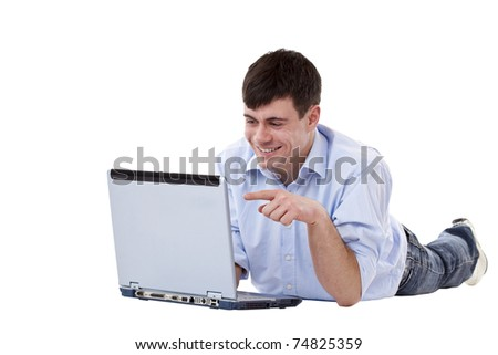 Handsome young man lies on floor and points on computer monitor. Isolated on white background. - stock photo