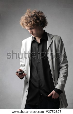 Handsome young man listening to music - stock photo
