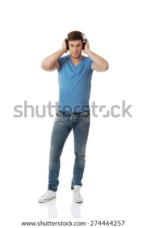 Handsome young man listening to music with headphones. - stock photo