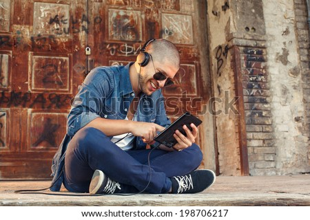 handsome young man listening to music with headphones via tablet PC - stock photo