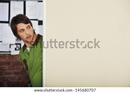 Handsome young man looking around corner in office - stock photo
