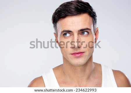 Handsome young man looking away over gray background - stock photo