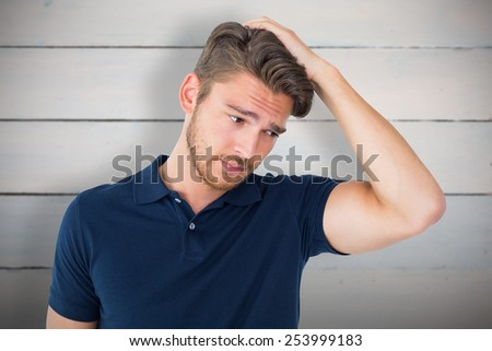 Handsome young man looking confused against painted blue wooden planks - stock photo