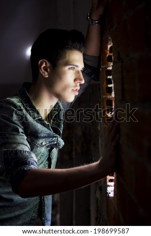 Handsome young man looking out through hole in brick wall - stock photo