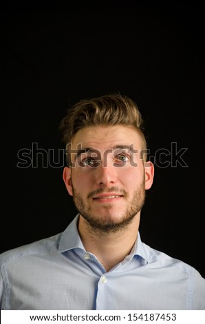 Handsome young man  looking up with nice expression, large copy-space, isolated on black background - stock photo
