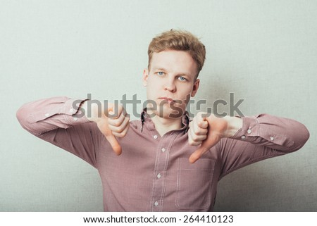 Handsome young man lowered his fist with the thumb down, disgruntled gesture - stock photo