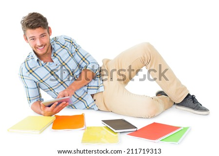 Handsome young man lying and studying on white background - stock photo