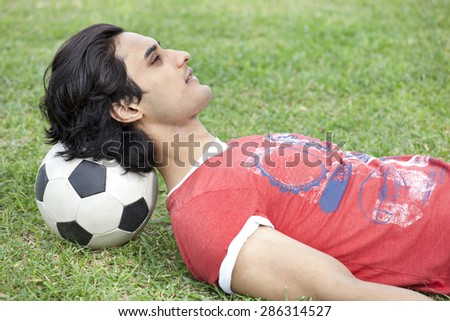 Handsome young man lying on back with head on soccer ball - stock photo