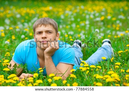 Handsome young man lying on the grass and looking away - stock photo