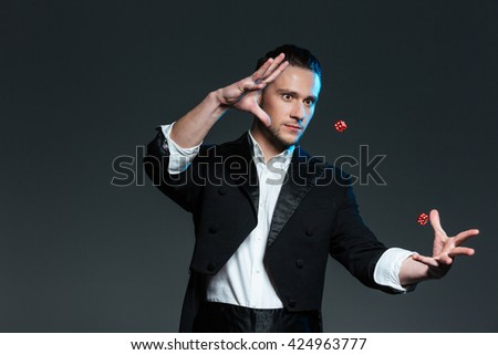Handsome young man magician showing tricks with flying dice over grey background - stock photo