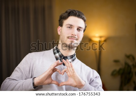 Handsome young man making heart sign with his hands and fingers - stock photo