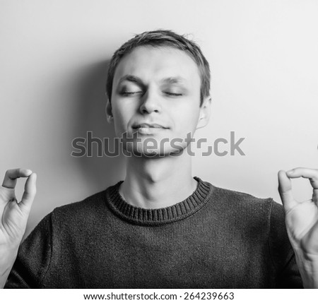 Handsome young man meditating, focus gesture.  - stock photo
