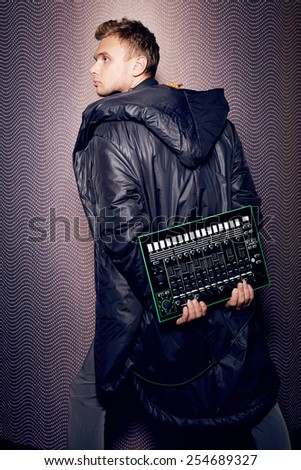 Handsome young man musician sexy singer with a microphone and headphones in a long black cloak stylish and trendy party DJ - stock photo