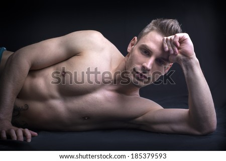 Handsome young man naked on floor. Athletic build - stock photo