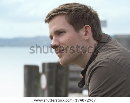 Handsome young man on a coastal pier Handsome young man on a coastal pier standing overlooking the water with a charismatic smile on his face and thoughtful expression, close up side view - stock photo