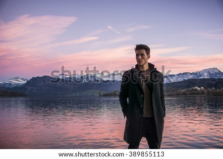 Handsome young man on Luzern lake's shore - stock photo